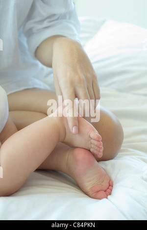 Mother touching baby's foot, cropped - Stock Photo