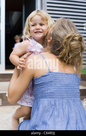 Mother embracing young daughter - Stock Photo
