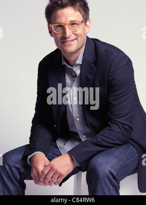 Fashionably dressed smiling man in his thirties wearing jeans and a stylish jacket - Stock Photo