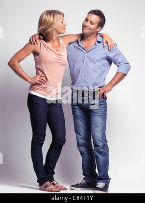 Smiling casually but with style dressed young man and a woman wearing jeans isolated on gray background - Stock Photo
