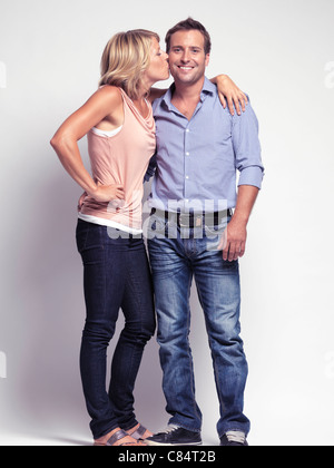 Smiling casually but with style dressed young people wearing jeans. Woman kissing a man on a cheek. Isolated on - Stock Photo