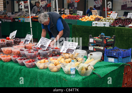 Man selling bowls of fruit on a market stall. England, UK, Britain - Stock Photo