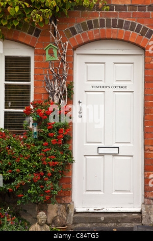 White front door of a red brick house known as Teacher's Cottge in Avebury in Wiltshire, England, UK - Stock Photo