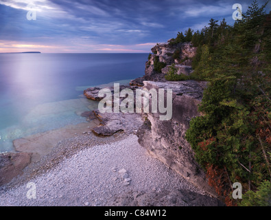 Beautiful sunset scenery of Georgian Bay rocky shore and cliffs inhabited by cedar trees. Bruce Peninsula National - Stock Photo