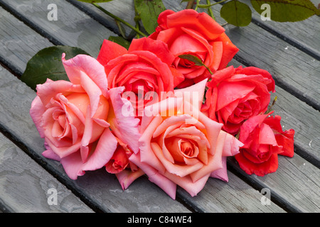 RED AND PINK CUT ROSES ON WOODEN SLATTED GARDEN TABLE - Stock Photo