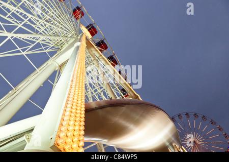 Fairground rides at night. Two big ferris wheels at Goose Fair, Nottingham, England, UK - Stock Photo