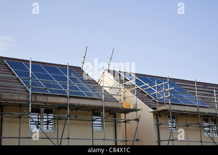 England, UK, Britain, Europe. Scaffolding for solar panels being installed on the roofs of new build houses - Stock Photo
