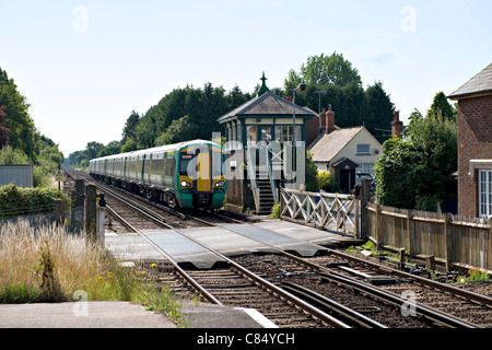 Electric Train passing over the level crossing at Plumpton Station, Plumpton, UK - Stock Photo