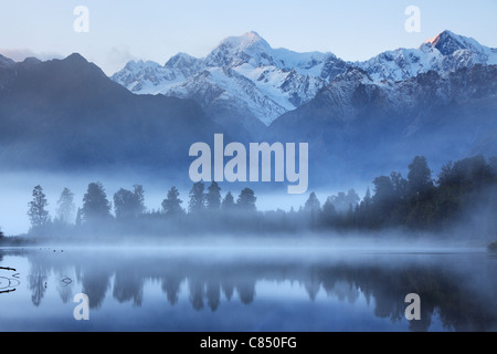 Reflection of Mt Cook (Aoraki) and Mt Tasman on Lake Matheson near Fox Glacier in New Zealand - Stock Photo