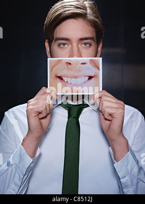 young business man holding photo of toothy smile on black background. Vertical shape, front view, waist up - Stock Photo