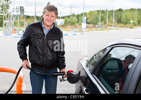 Russian mature man filling the modern car with gasoline in gas stations in Russia - Stock Photo