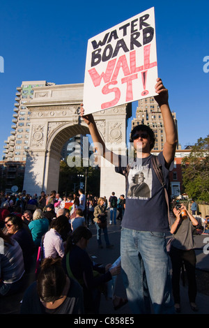 Occupy Wall Street protester in Washington Square Park holding a sign that reads 'Water Board Wall St!' - Stock Photo