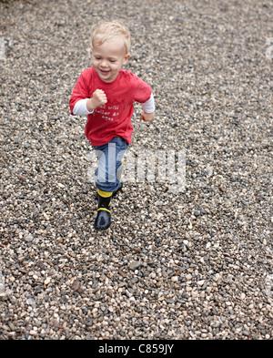 Toddler boy running on gravel - Stock Photo