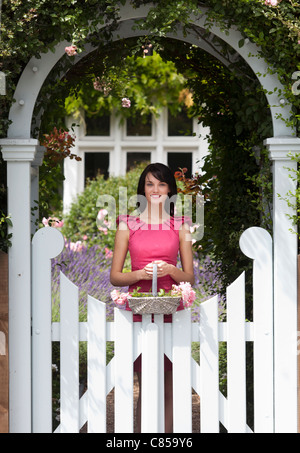 Woman carrying basket under arch - Stock Photo