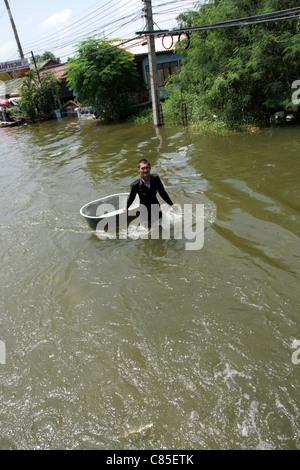 Thai people wading through floodwaters on street , Ayutthaya , Thailand - Stock Photo