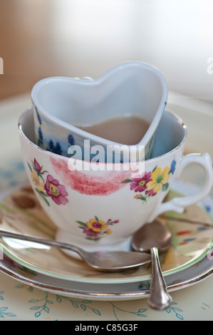 Messy Cups of tea in each other, one of them smudged with lipstick the other heart-shaped - Stock Photo
