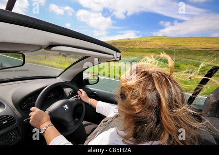 Open top sports car driven by female on open country road