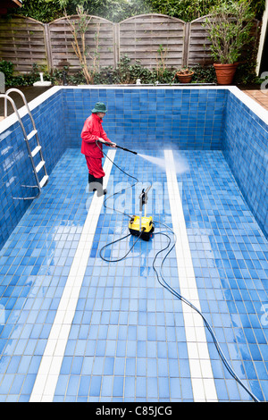 Man Cleaning Swimming Pool, Germany - Stock Photo