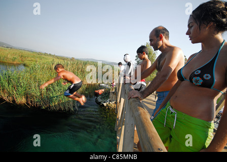 AKYAKA, TURKEY. A young boy jumping off a bridge into the Azmak river, with his family watching. 2011. - Stock Photo