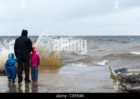 Father and his small children watching at waves crashing ashore during an autumn storm in Nallikari, Oulu, Finland - Stock Photo