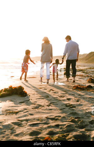 Young family walking along the beach - Stock Photo