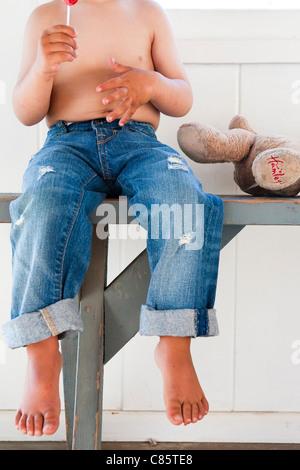 Shirtless boy eating a lollipop - Stock Photo