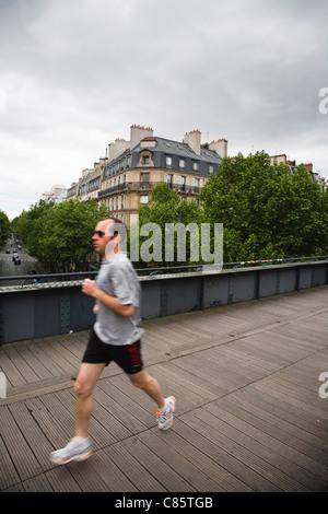 A jogger runs along the top of Le Viaduc des Arts, France - Stock Photo