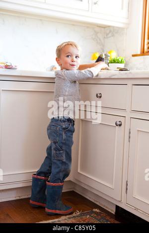 Little boy helping in kitchen - Stock Photo