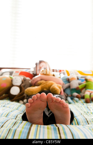 Boy laying on bed with stuffed animals - Stock Photo