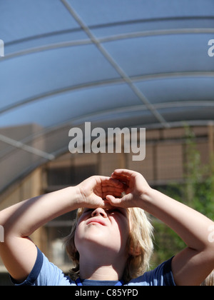 Little boy looking up shielding his eye from the sun - Stock Photo