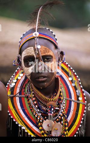 Lolgorian, Kenya. Siria Maasai Manyatta; woman with white and red ochre face paint, brightly coloured beadwork adornments. - Stock Photo