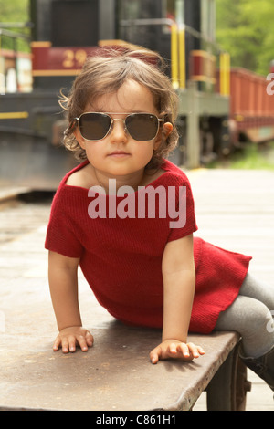 Girl in red dress and aviator sunglasses - Stock Photo