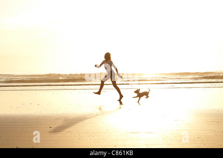 Girl running on the beach with her dog in the morning sunrise - Stock Photo