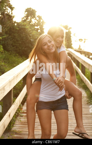 Sisters playing piggy back on the beach boardwalk - Stock Photo