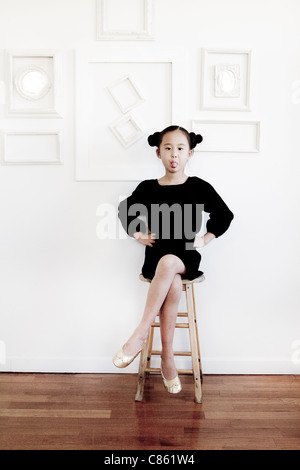 Little girl on stool sticking out her tongue - Stock Photo