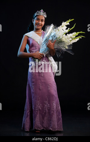 Teenage beauty queen holding a bouquet - Stock Photo