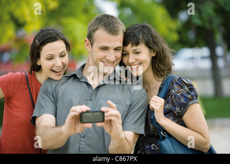 Man photographing himself with two female friends using cell phone - Stock Photo