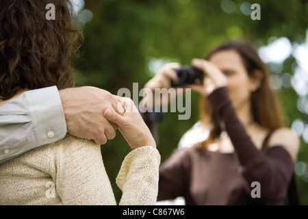 Couple holding hands as woman photographs them, cropped - Stock Photo