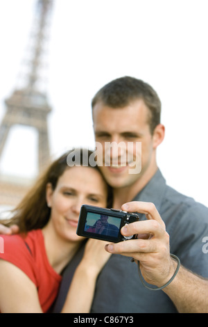 Couple photographing selves in front of Eiffel Tower, Paris, France - Stock Photo