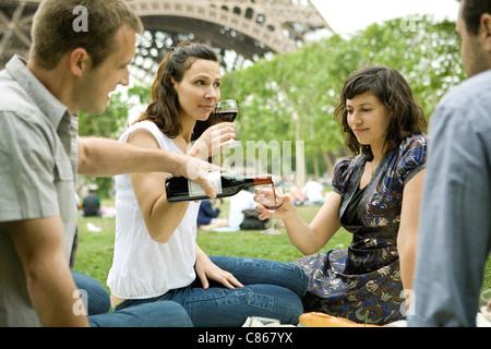 Friends enjoying wine at picnic near Eiffel Tower, Paris, France - Stock Photo