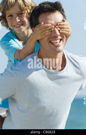 Boy covering father's eyes with hands