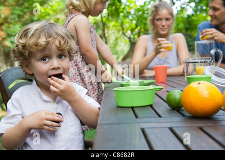 Boy enjoying outdoor snack with his family - Stock Photo