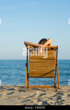 Woman relaxing in lounge chair on beach - Stock Photo