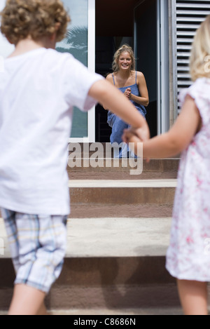 Young siblings holding hands, running toward mother - Stock Photo
