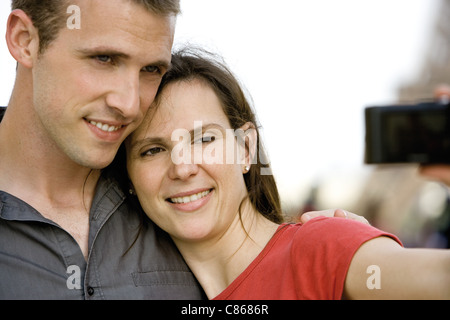 Couple photographing themselves outdoors - Stock Photo