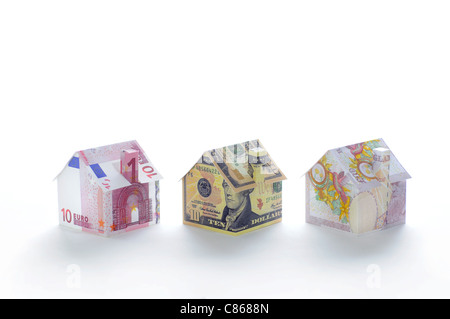 Model houses folded with different currencies - Stock Photo