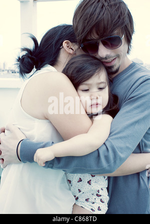 Parents and young daughter embracing - Stock Photo