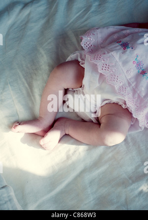 New born baby girl's legs, cropped, directly above - Stock Photo