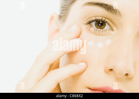 Woman applying undereye cream, close-up, cropped - Stock Photo