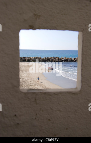 View of beach and ocean through window - Stock Photo